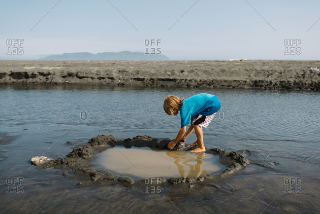 A boy builds a pool of water at the shore