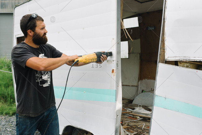 A man tears apart a trashed travel trailer