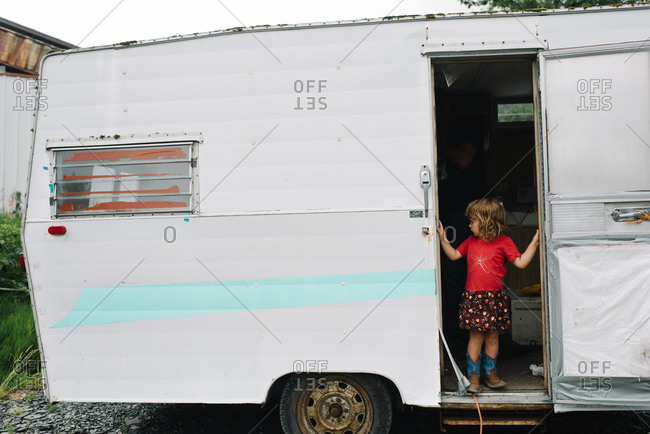 A little girl stands in a travel trailer door