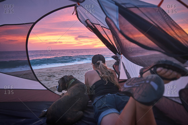Woman and dog looking out tent at beach sunset