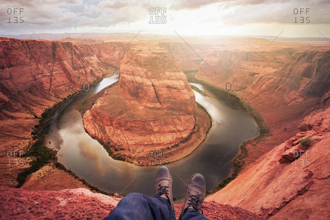 Feet dangling over canyon with river