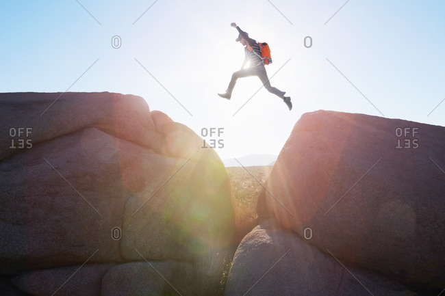 Man jumping between boulders in sunlight