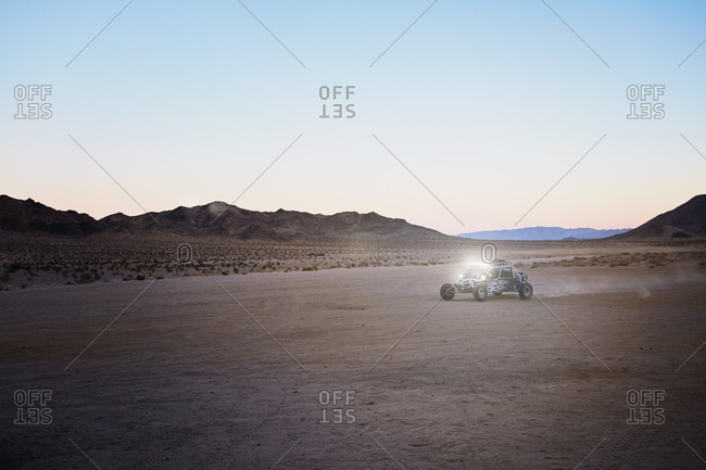 Racing buggy driving through desert plain