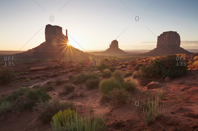 Sun setting near rock tower formations