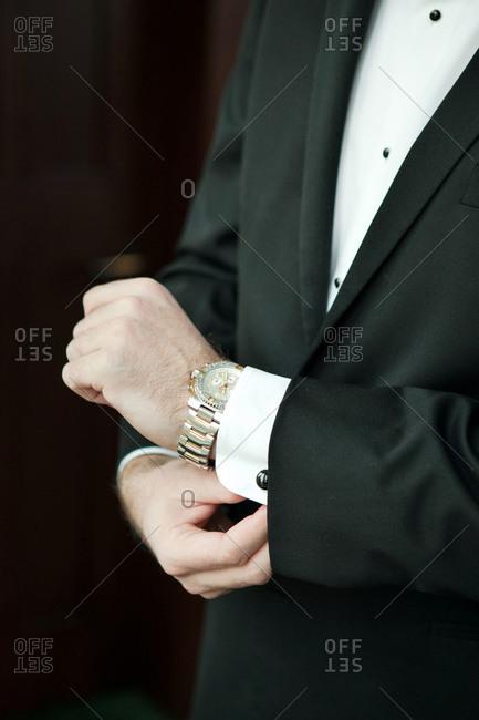 Groom adjusting his tux cuff