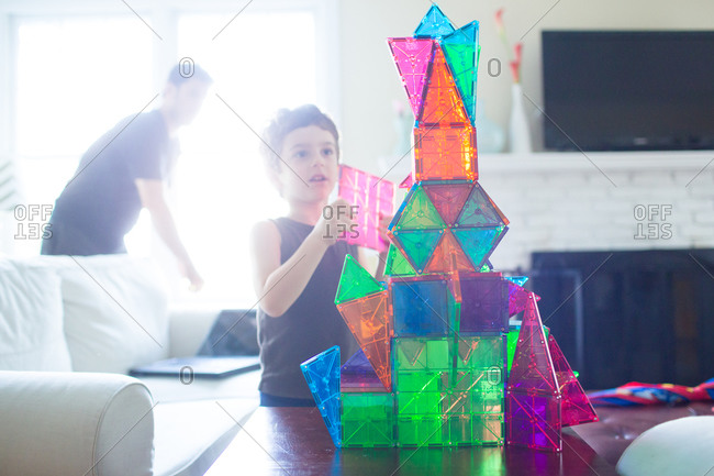 Little boy building a plastic castle with his father
