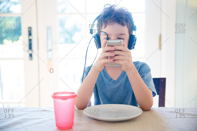Little boy sitting a table looking at an MP3 player