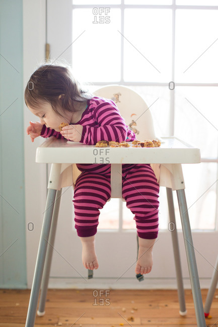 Little girl sitting in a high chair looking down at the floor