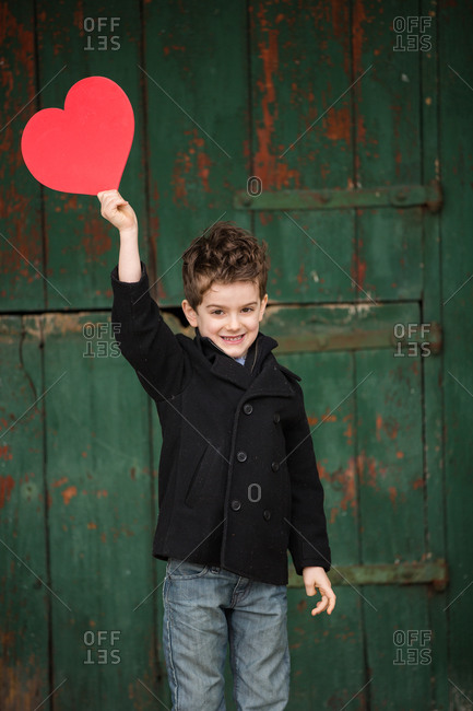 Little boy holding a paper heart in the air