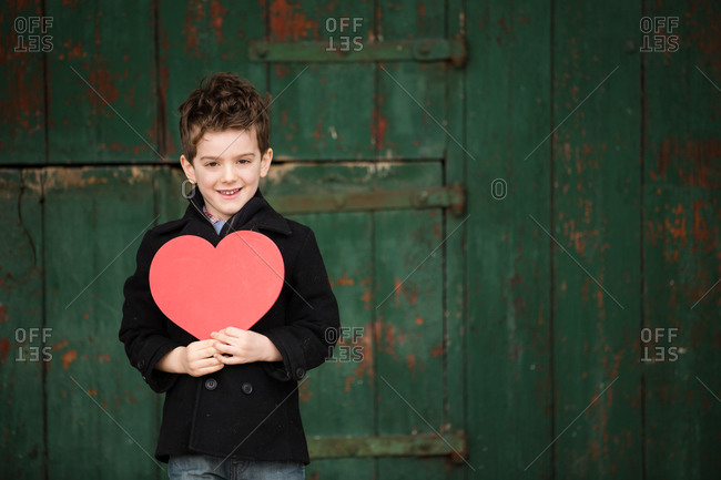 Little boy holding a paper heart to his chest