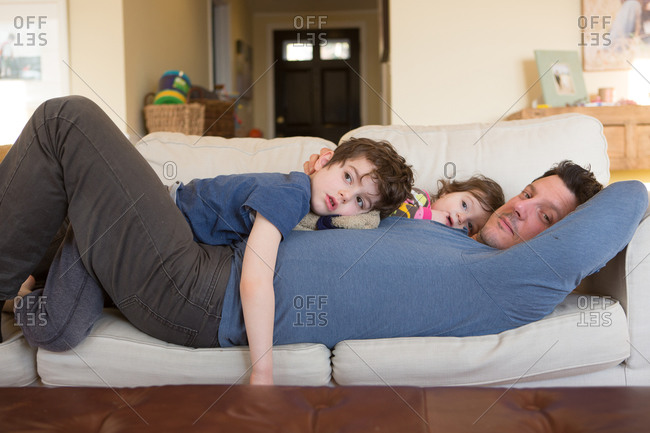 Father lying on a couch with son and daughter