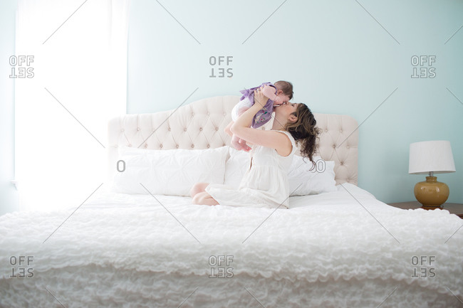 Mother holding her baby girl in the air and kissing her