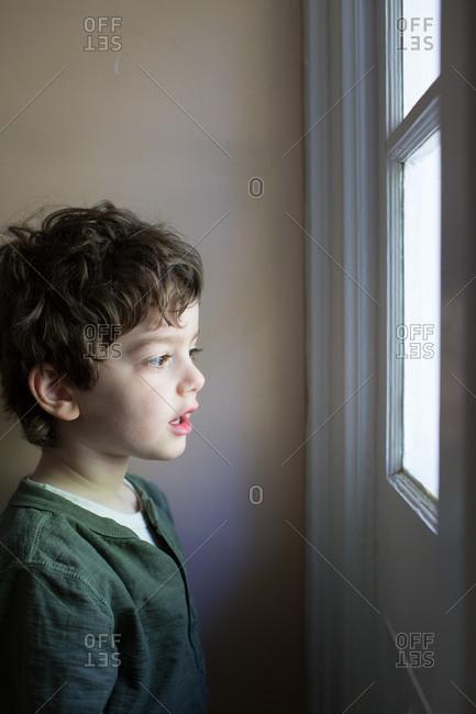 Little boy looking out a window