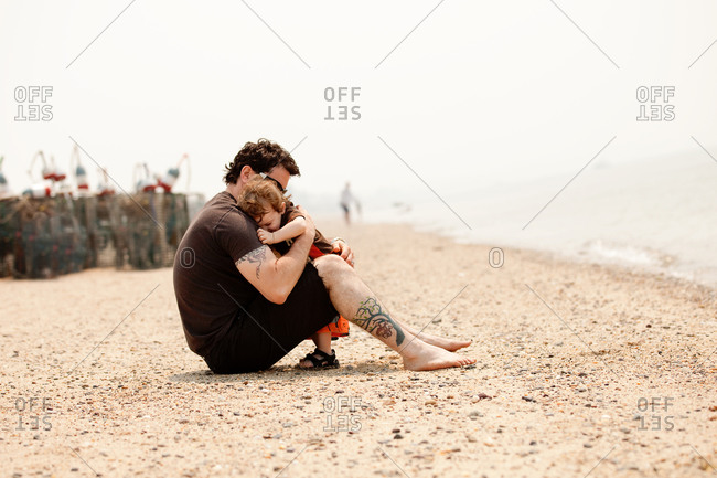 Father sitting on a beach holding his son