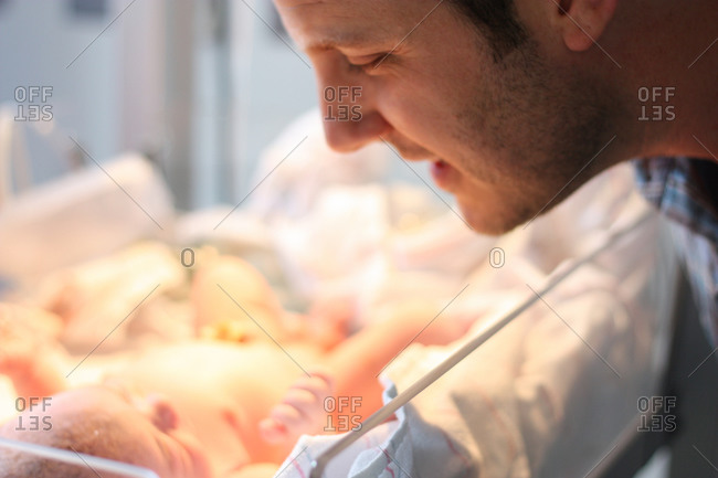 Father looking at newborn son in hospital bassinet
