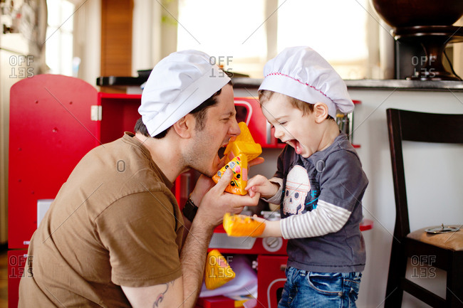 Father and son playing with toy kitchen and pizza