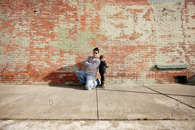 Father and son posed back to back in front of a brick wall