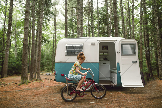 Girl riding bike by camper in woods