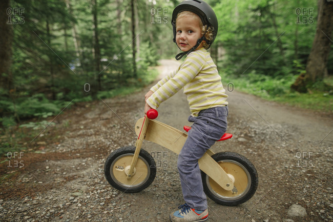 Boy sitting on scooter on forest trail