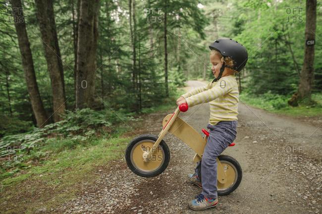 Boy popping a wheelie on forest trail