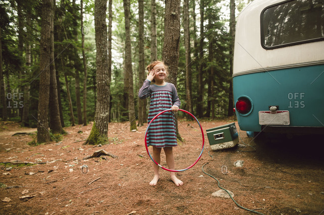 Girl laughing with hula hoop by camper in woods