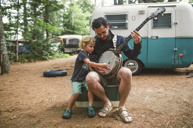 Boy and dad playing banjo at campsite