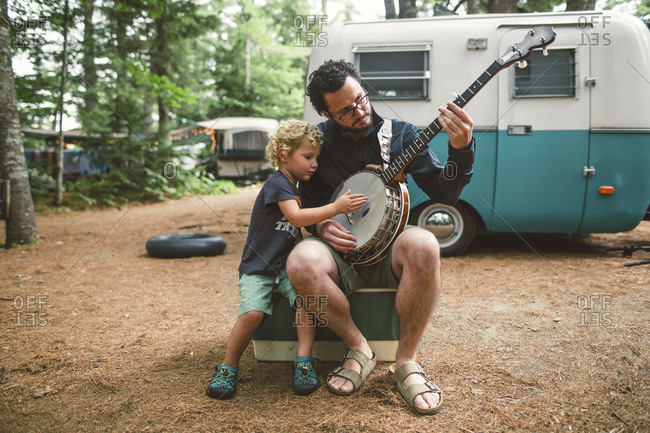 Boy and dad with banjo at campsite