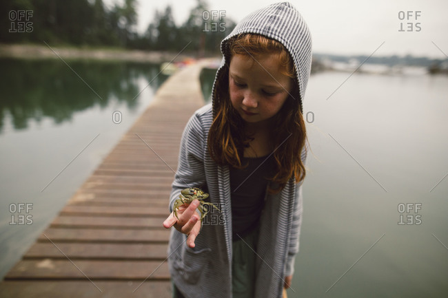 Girl on lake pier holding a crab