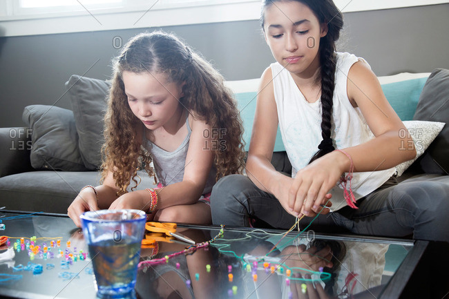 Girls making beaded jewelry on a glass coffee table