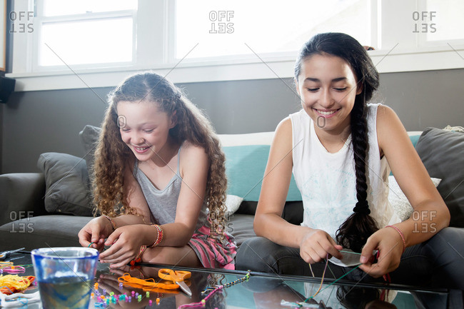 Two girls making jewelry on a glass coffee table