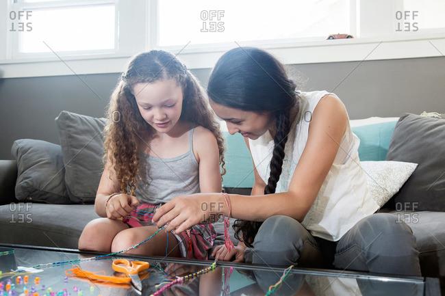 Girls sitting on a sofa making jewelry