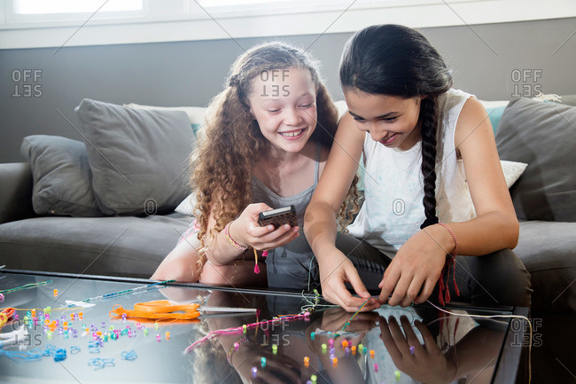 Girl making jewelry while her sister checks her phone