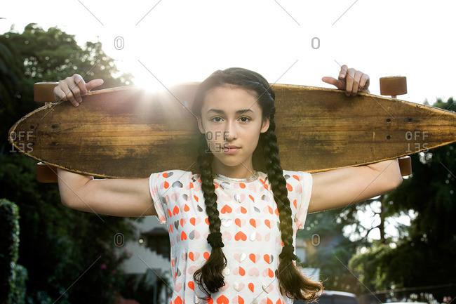 Girl holding a skateboard on her shoulders