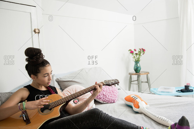 Girl sitting on her bed playing a guitar
