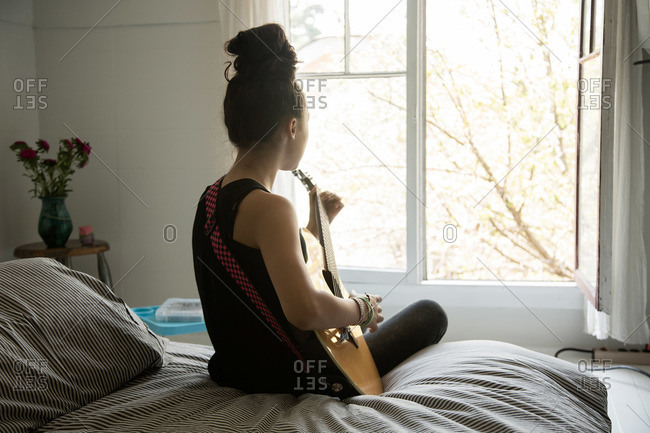 Girl sitting on the edge of her bed playing a guitar