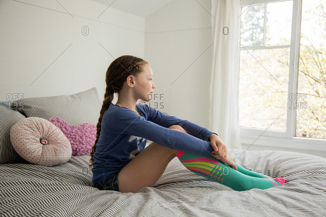 Girl sitting on her bed looking out a window