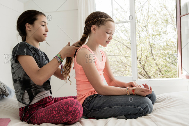 Girl sitting on a bed braiding her sister's hair