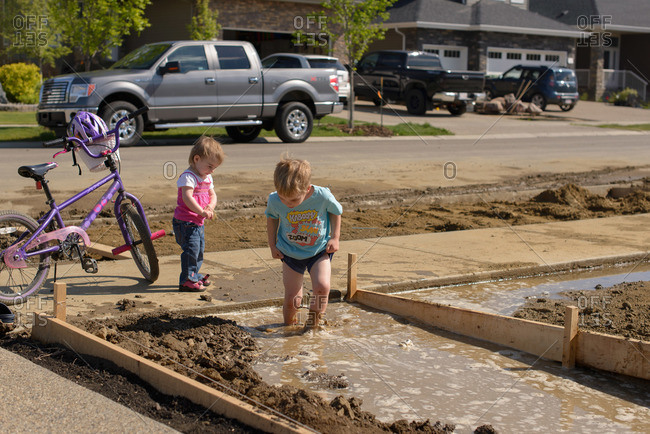 Two toddlers play in a muddy house foundation
