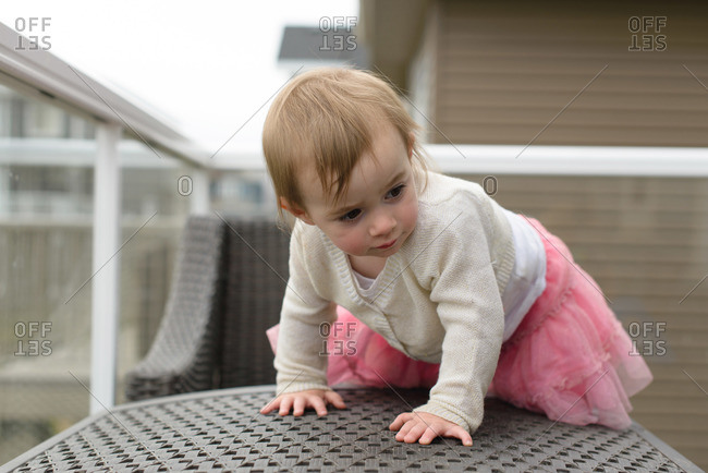 A little girl climbs on patio furniture