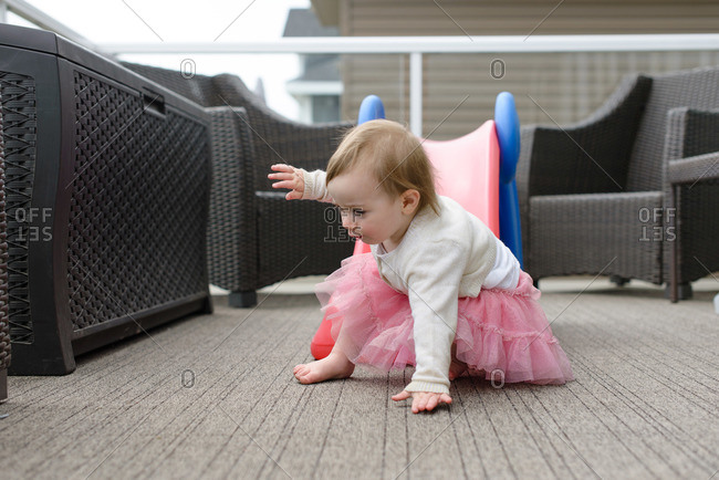 A little girl crawls off of a slide on a patio