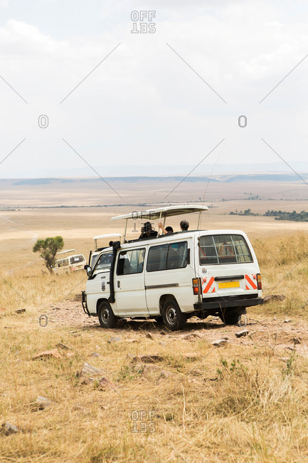 Tourists ride in a van to see African wildlife in the Maasai Mara, Kenya