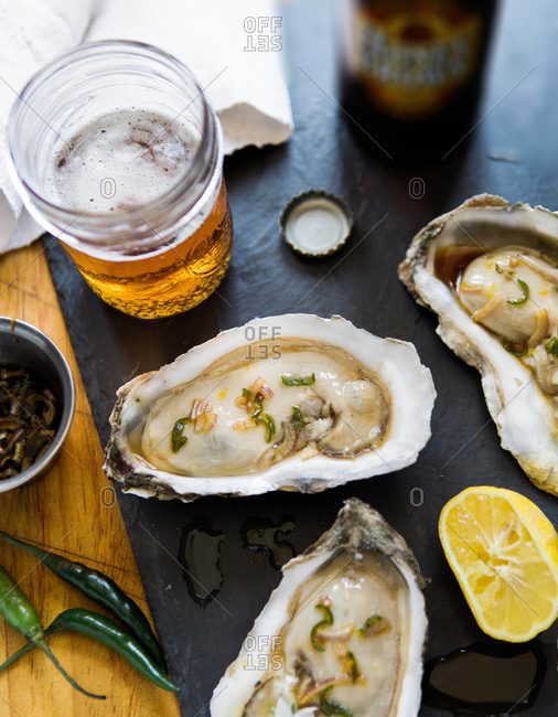 Overhead view of oysters on the halfshell with a glass of beer
