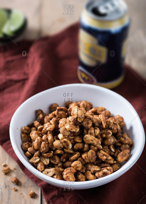 Bowl of spiced nuts on cloth with a can of beer