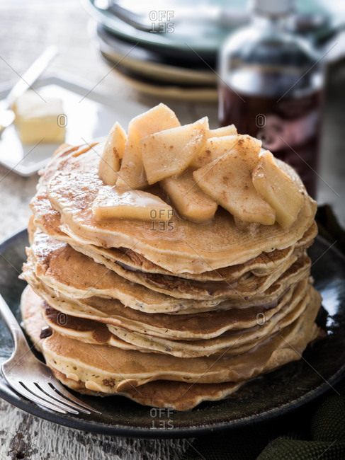 Stack of pancakes topped with cinnamon apples