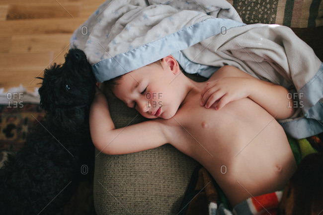 A boy naps on a couch while his dog cuddles him