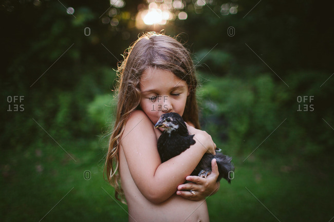 A little girl kisses a baby chicken