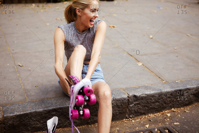 A young woman laughs while putting on a rollerskate