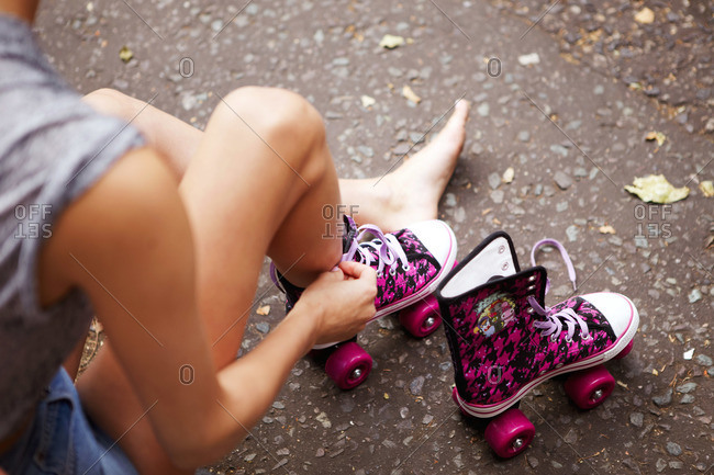A woman puts on pink rollerskates