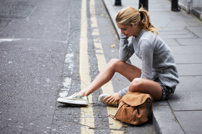 A young woman sits on the sidewalk in a city