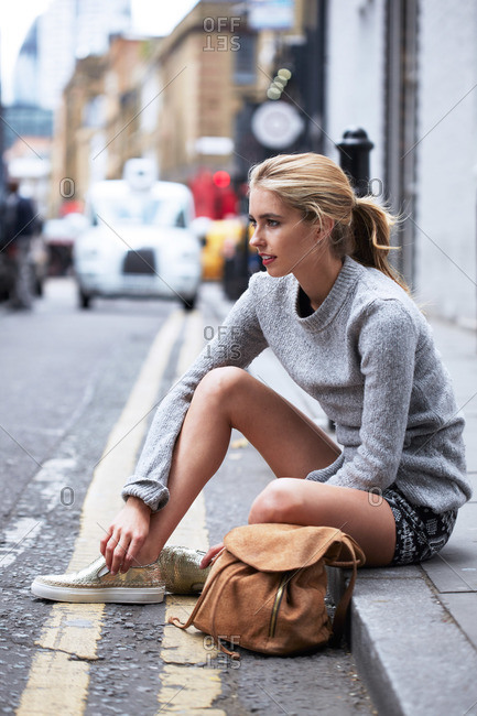A young woman sits on a curb in a city